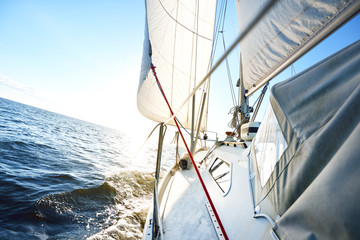 Close-up of the yacht in the sea, a view from the deck to the bow and sails. A clear sunny day, Latvia