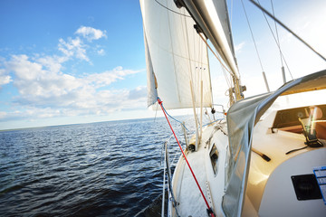 A view from the yacht's deck to the bow and sails on a sunny summer day. Baltic sea