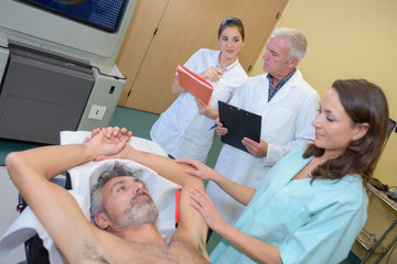 Nurse reassuring patient with arms raised over his head