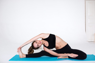 Flexible woman exercising on a fitness mat