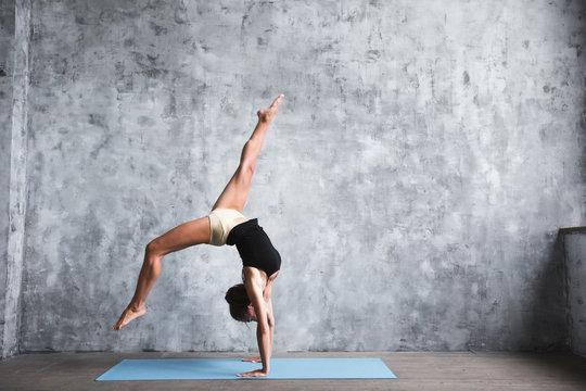 Dark-haired woman doing handstands