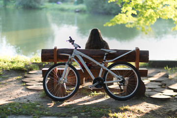 a girl with long hair sitting on a bench under a tree by the lake while watching the sunset, having arrived on a bicycle