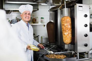 Mature man chef wearing uniform preparing kebab