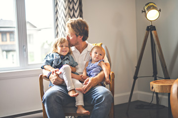 Portrait of happy son and baby daughter with father at home