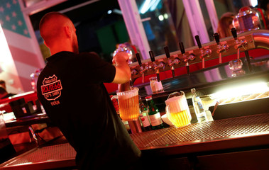"A barkeeper pours Budweiser beer from the tap at ""Route 66 Diner"", which offers American diner food, in Berlin"