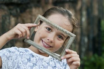 Портрет девочки. Девочка смотрит через фоторамку