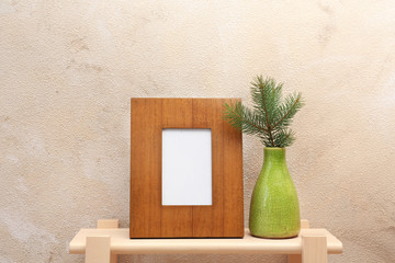 Blank frame and vase with fir branch on table near color wall. Mock up for design