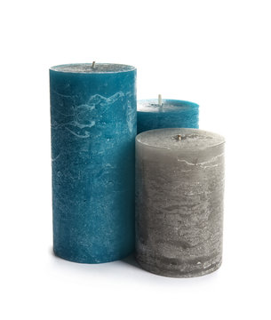 Different decorative wax candles on white background