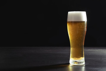 Glass with cold tasty beer on dark background