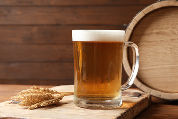 Glass mug with cold tasty beer and malt on wooden table