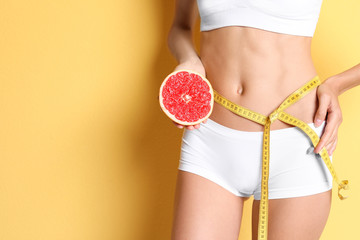Young slim woman in underwear with measuring tape and grapefruit on color background. Weight loss diet results