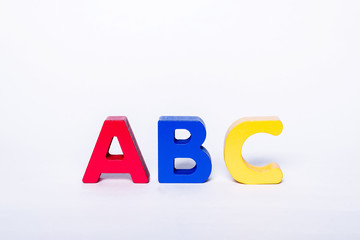 ABC letters in different colors on an isolated white background. Wooden, colorful, children's letters. The concept of learning to read and write.