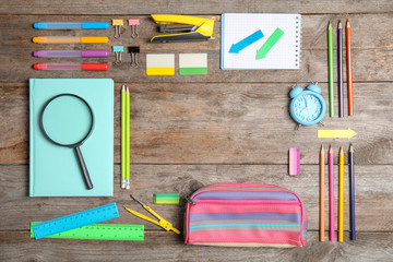 Different school stationery with space for design on wooden background, flat lay