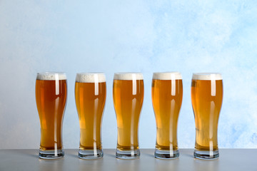 Glasses with beer on table against color background