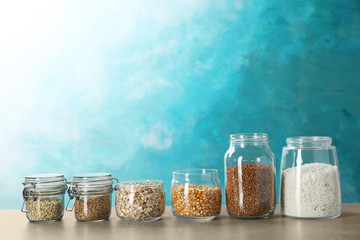 Jars with different types of grains and cereals on table