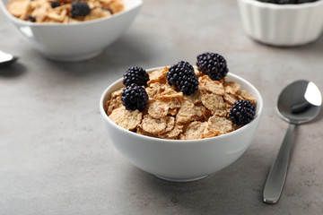 Bowl with cornflakes and blackberries on gray table. Whole grain cereal for breakfast