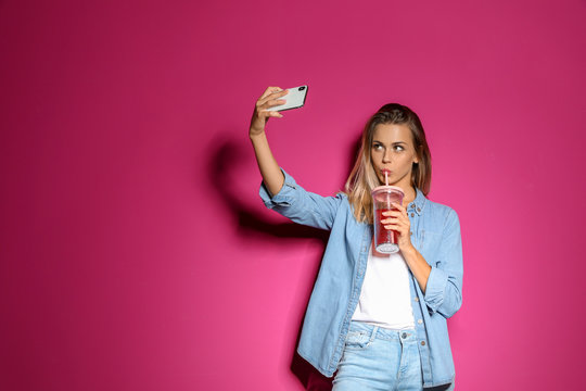 Beautiful woman with tasty drink taking selfie on color background