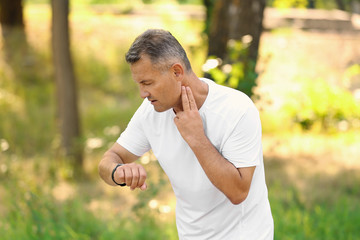 Man checking pulse outdoors on sunny day
