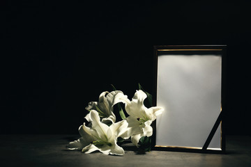 Funeral photo frame and lily flowers on dark background