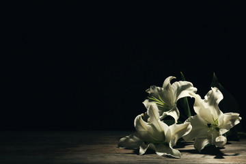 Beautiful lilies on dark background with space for text. Funeral flowers Wall mural
