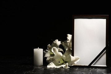 Funeral photo frame, burning candle and lily flowers on dark background