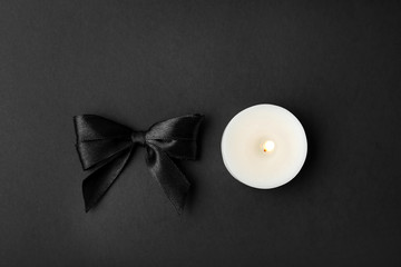 Ribbon and candle on black background, top view. Funeral symbols