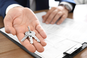 Real estate agent with keys at table in office, closeup