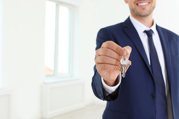 Real estate agent holding key on blurred background, closeup