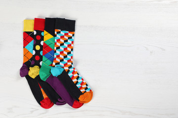 Fototapete - Flat lay composition with different socks and space for design on light wooden background