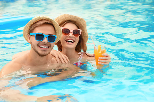 Young couple in pool on sunny day