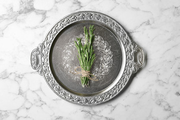 Plate with rosemary on marble background, top view. Aromatic herbs