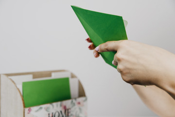 Female hands pull a green envelope from the package. The concept of reading e-mails, sending paper letters. On the table, on a light background, there is a laptop and a telephone.