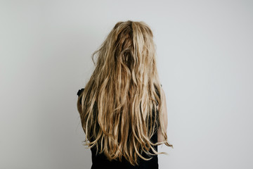 A view of the hair from the back of a woman, a girl's figure isolated on a bright gray background. The back of a modern woman dressed in a black blouse and pants, blond fair hair.