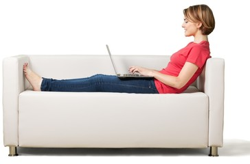 Young cute woman with laptop on sofa isolated on white