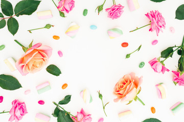 Round frame of Roses flowers and marshmallow with colorful candy on white background. Flat lay, top view.