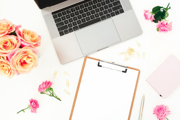 Silver laptop, roses flowers and clipboard on white background. Flat lay. Top view. Women's blog concept
