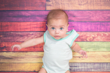 Baby boy in studio with colorful wooden background
