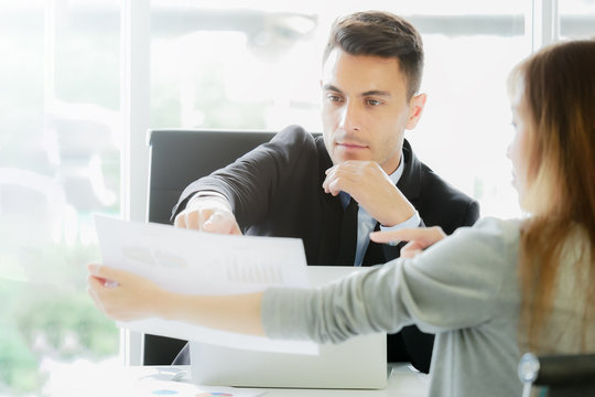 Financial report analysis and reviewing concept :CFO or chief financial officer sees financial summary reports with his secretary and discusses about future growth and improvements