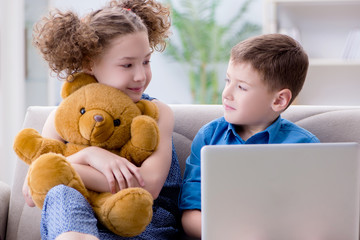 Two kids sitting at laptop at home