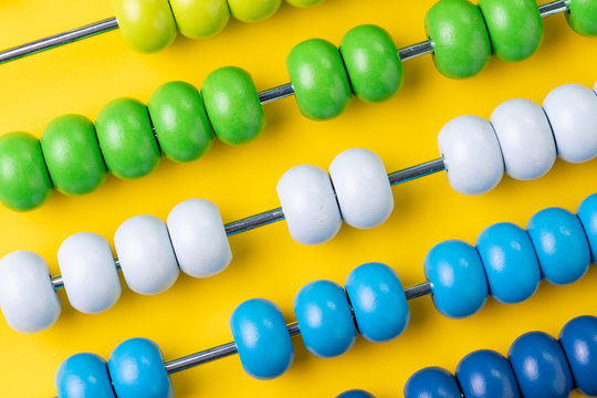 Colorful wooden abacus beads on yellow background, business financial or accounting profit and loss concept, or use in education school arithmetic symbol