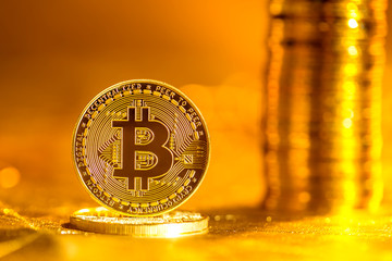 Bitcoin cryptocurrency coin with on a bright gold background
