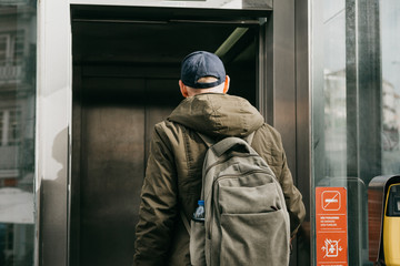 A tourist man with a backpack uses a street elevator in Porto in Portugal to go down to the metro.
