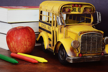 Books, apple, crayons and student bus