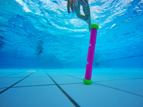 Sports little girl dives to the bottom of the pool and collects toys on a blue background. Shooting under water. Landscape orientation
