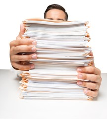 Tired Businessman near heap of papers  on background