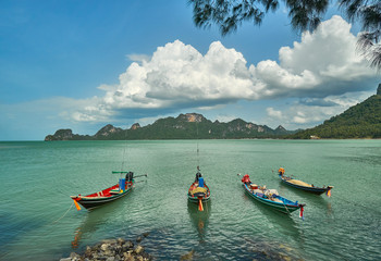 Fishing boats off the coast in a green sea lagoon against the backdrop of mountains and a blue sky in a sunny day