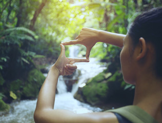 The woman making frame round the waterfall with her hands in the rain forest,copy space,warm retro tone.