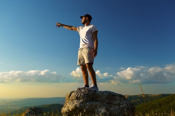 Man Pointing on Mountain Top