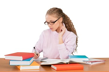 Girl Sitting Behind a Desk with a Books and Writing in Note Pad