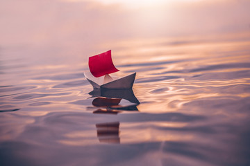 paper boat with red sail floating on water